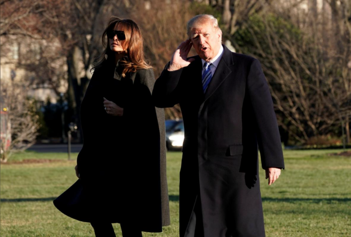 U.S. President Donald Trump listens to reporters as walks with first lady Melania Trump on South Lawn of the White House upon their return to Washington, U.S., from Palm Beach, Florida