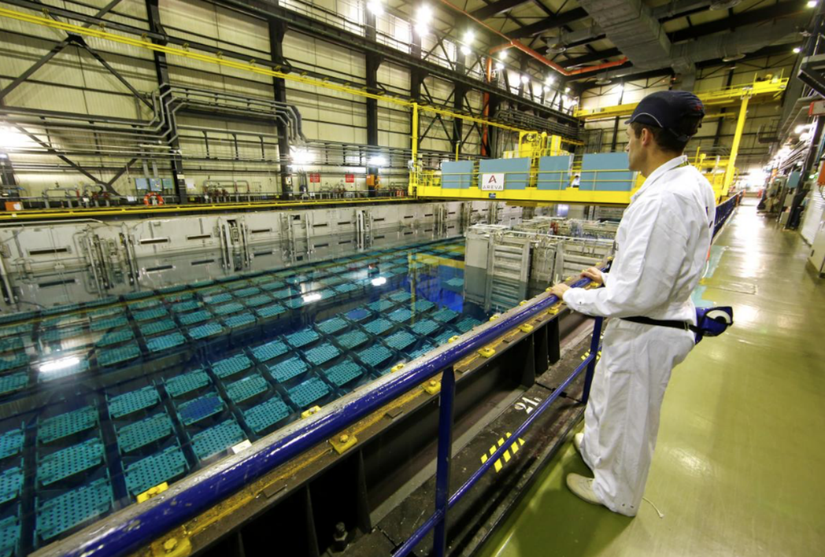 FILE PHOTO: A technician looks at the pool storage where spent nuclear fuel tanks are unload in baskets under 4 meters of water to decrease temperature as part of the treatment of nuclear waste at the Areva Nuclear Plant of La Hague, near Cherbourg, western France, April 22, 2015. REUTERS/Benoit Tessier/File Photo
