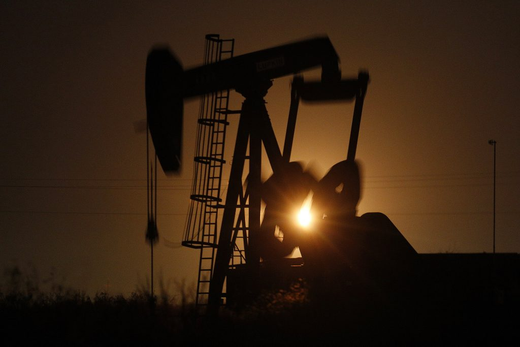 The silhouette of an electric oil pump jack is seen at dusk in the oil fields surrounding Midland, Texas, U.S., on Tuesday, Nov. 7, 2017. Nationwide gross oil refinery inputs will rise above 17 million barrels a day before the year ends, according to Energy Aspects, even amid a busy maintenance season and interruptions at plants in the U.S. Gulf of Mexico that were clobbered by Hurricane Harvey in the third quarter. Photographer: Luke Sharrett/Bloomberg
